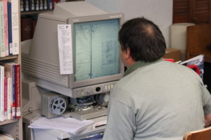 A researcher looking at microfilm