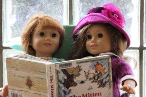 Two dolls reading a book