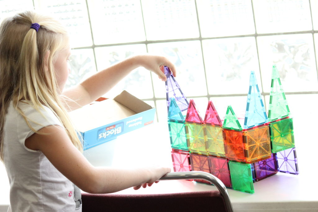 A girl building with plastic toys