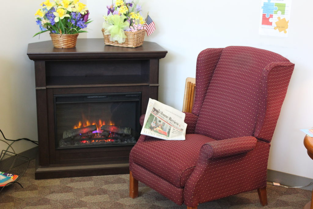 A comfy armchair near a fireplace for reading