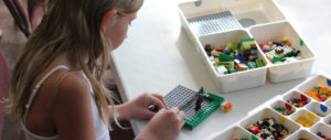 A little girl working with Legos